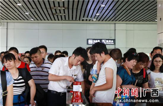 桂林火车站工作人员耐心引导旅客使用闸机检票进站。 李洪锐 摄