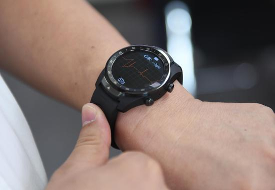 图为:工作人员展示心率监测智能设备。  王刚 摄