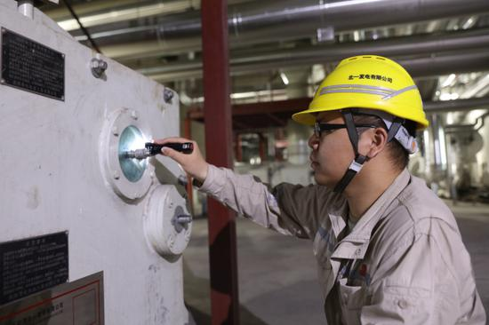 图为企业职工检查磨煤机运转情况。