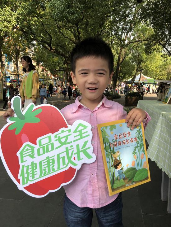 图为:同学展示《食品安全与健康成长读本》。 主办方供图
