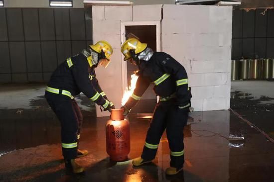 圖為爆燃后消防員將仍在著火的煤氣拿出。顏杰 攝