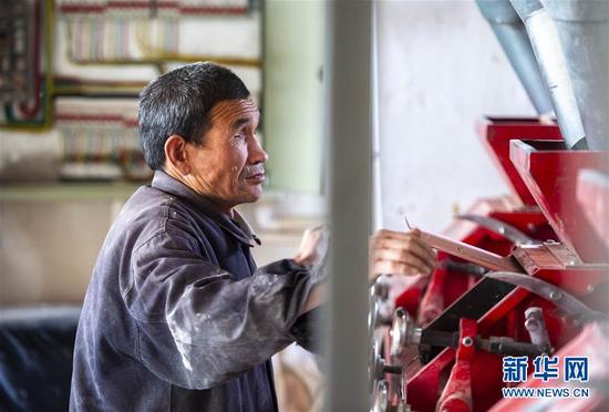 """马腾俊在操控电动磨面机(10月25日摄)。    57岁的马腾俊家住宁夏回族自治区吴忠市红寺堡区柳泉乡羊坊滩村,从小因病双目失明,他自力更生开起了磨坊,依靠记忆力和触觉能够熟练操作机械和电路开关,被称为""""能人""""如今他除了磨坊的收入之外,家里还养了5头牛,种了10亩玉米和3亩黄花菜,生活越过越好,成了当地脱贫致富的知名人物。如今他除了磨坊的收入之外,家里还养了5头牛,种了10亩玉米和3亩黄花菜,生活越过越好,成了当地脱贫致富的知名人物。 新华社发(杨植森 摄)"""