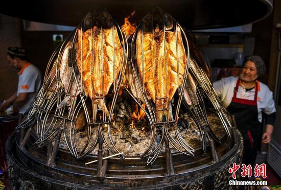 """11月1日,位于乌鲁木齐市二道桥的新疆国际大巴扎美食街正式开启冬季运营模式。在未来长达半年的冬季,经过升级改造后的透明全景暖房""""冰屋夜市"""",将为游客提供具有新疆特色的就餐环境。夜市中21个美食档口,可加工制作超过170种新疆美食,让游客一站即可吃遍新疆美食。图为""""冰屋夜市""""中的新疆烤鱼档口。中新社记者 刘新 摄"""