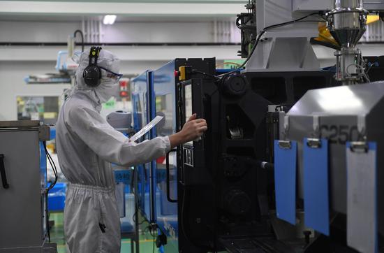 图为:泰尔茂医疗产品(杭州)有限公司工作人员在无人车间内设置设备参数。 王刚 摄