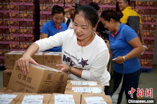 广西螺状元食品科技股份有限公司的工人正在贴快递单,准备发货。 朱柳融 摄