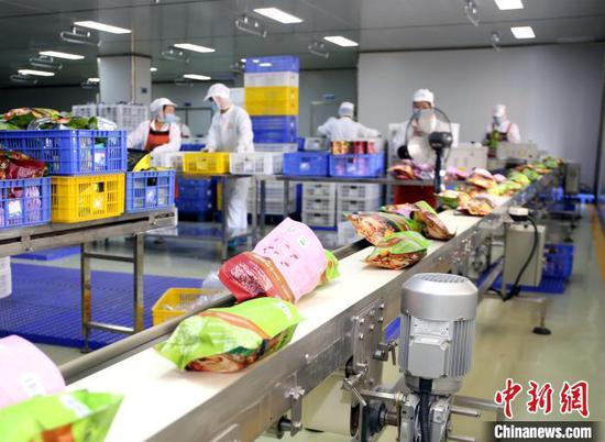 广西螺状元食品科技股份有限公司生产线,一袋袋包装好的螺蛳粉,通过传送带传送到打包车间。 朱柳融 摄