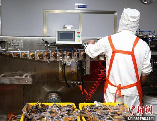 广西螺状元食品科技股份有限公司生产线,工人正在汤料包装设备旁工作。 朱柳融 摄