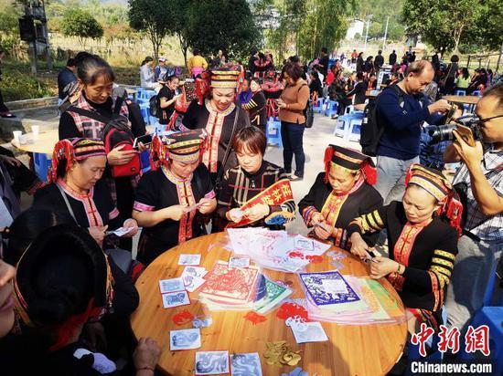 11月12日,廣西興安縣華江瑤族鄉盤王節當天,瑤族大媽在學剪紙藝術。 彭康生 攝