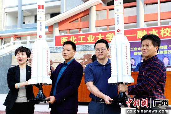 西北工業大學留聯會向兩所學校贈送科技周火箭模型。