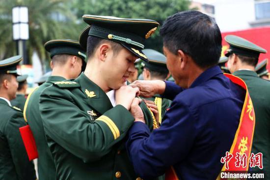 军属给晋衔干部佩戴新警衔。 朱柳融 摄