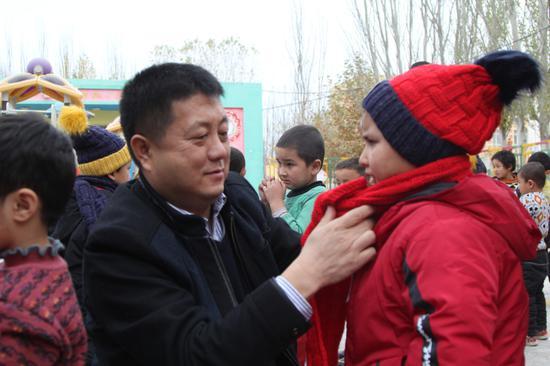 志愿者代表为幼儿赠送衣服。