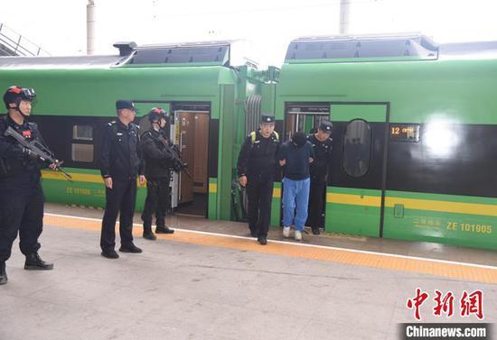 民警将电信诈骗犯罪嫌疑人带下火车。杨文涛 摄
