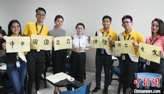 图片展作品之一,展示在菲的孔子学院教师教授菲律宾学生写汉字。主办方供图
