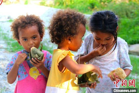 图片展作品之一,展示中国端午节期间菲律宾孩童吃中国粽子。主办方供图