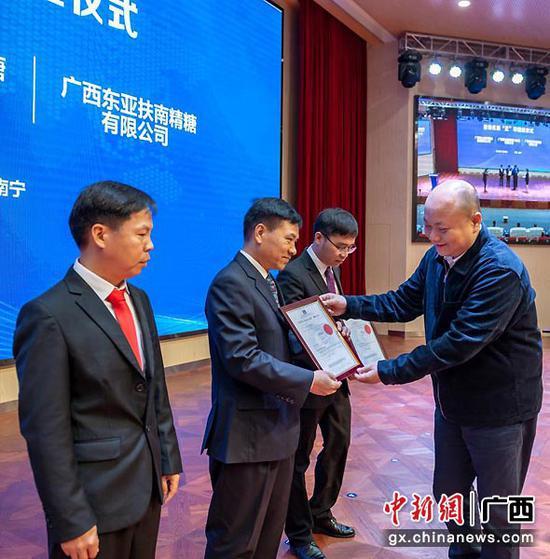 """图为广西-香港标准及检定中心有限公司负责人为企业颁发香港优质""""正""""印证书。"""