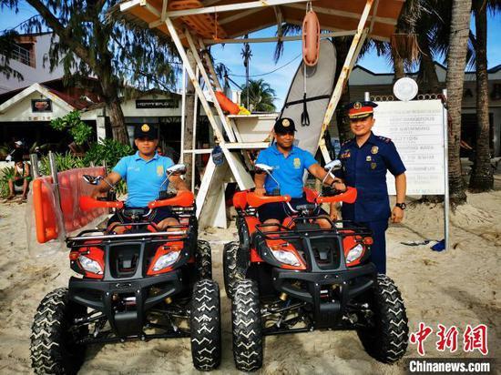 在阿克兰警察局局长PLTCOL JONATHAN PABLISO见证下,当地警察,首次驾驶鲜红车身、黑胶轮宽大、侧挂救护担架的沙滩救护摩托,组队巡逻。 关向东 摄