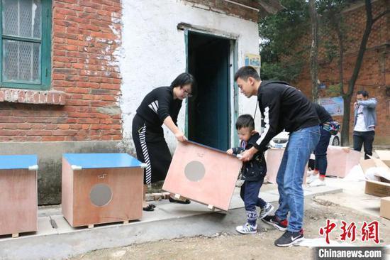 图为一家三口参加搭建猫屋公益活动。 林馨 摄