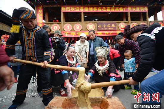 图为当地侗族同胞在打年粑。 潘志祥 摄