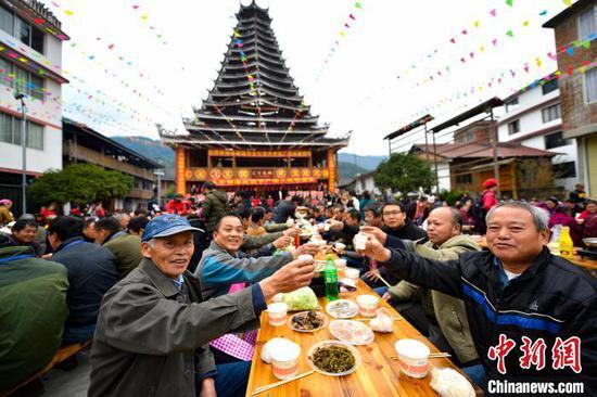 图为当地侗族同胞与八方宾客共享百家宴。 潘志祥 摄