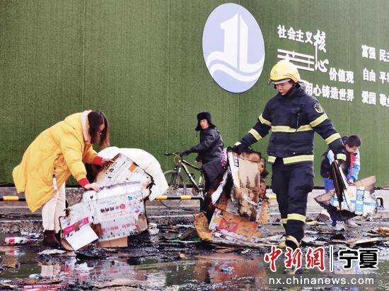 市民和学生帮助消防员收拾马路上的火灾垃圾。李鹏博 摄