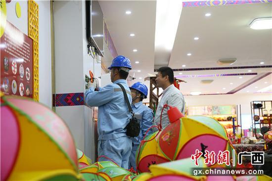 南方电网工作人员对靖西绣蕴坊绣球文化有限公司电路检修。陈伯鑫 摄