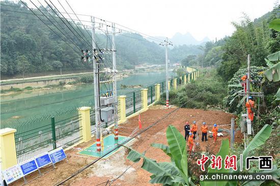 大新县硕龙镇归春河畔,施工人员正在拆除旧变压器,旁边的新变压器已经安装完成。陈海堂   摄