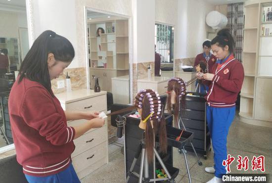 12月3日,桂林市聋哑学校的学生在学习美发技能。欧惠兰 摄