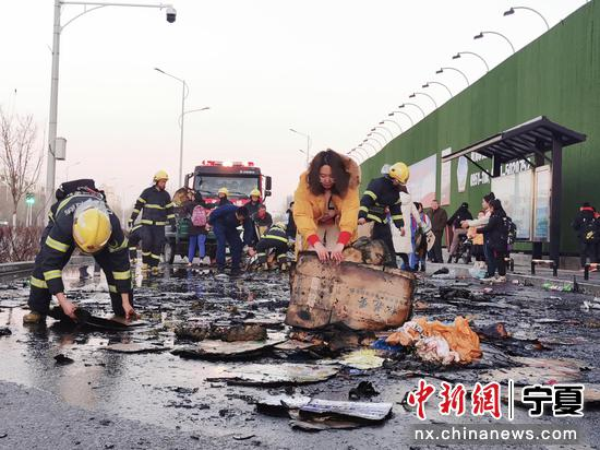 市民和学生帮助消防员收拾马路上的火灾垃圾。