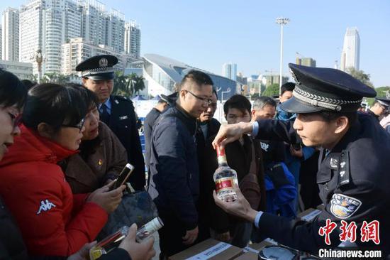 警方教民众辨认假冒伪劣五粮液。蒋雪林 摄