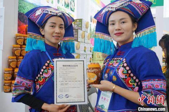 身着少数民族服饰的广西姑娘展示产自广西横县的有机木瓜丝。 欧惠兰 摄