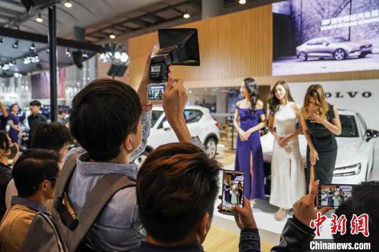 图为参观者拍摄车模。本次车展共有800余名车模助阵。 陈冠言 摄