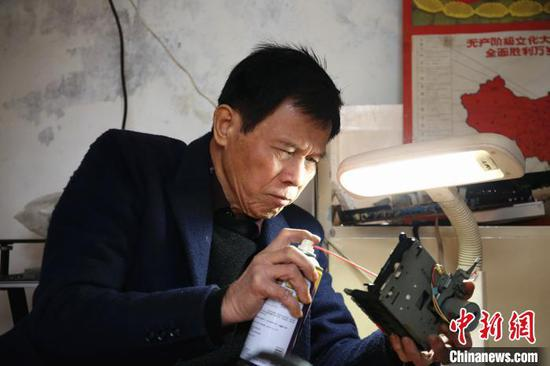 谢志宽在修理收音机零部件。 朱柳融 摄