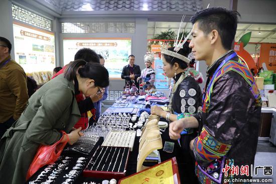 12月7日,在广东省廉江市举办的红橙节暨家电博览会上,游客在选购苗族银饰。