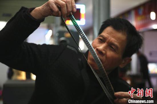 谢志宽在查看电影胶带。 朱柳融 摄