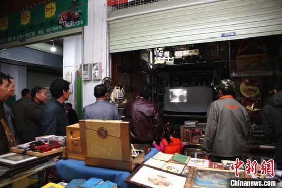 人们围在谢志宽的门店看电影。 朱柳融 摄