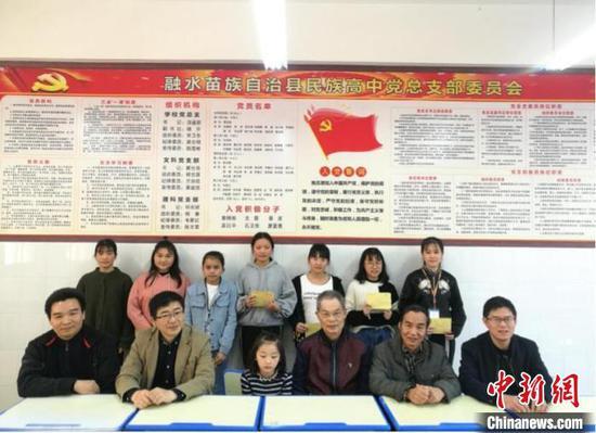2018年3月10日,黄富荣在融水民高捐资助学并与学生合影。 受访者供图