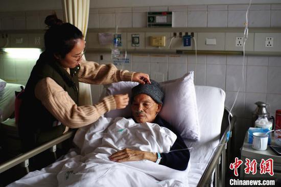贾习花到医院看望并照顾黄富荣。 邹振远 摄