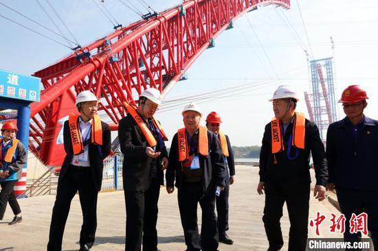 图为参加世界大跨度拱桥建设技术大会的专家现场观摩广西平南三桥建设情况。 黄南 摄