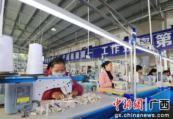 村民在服装生产线上作业。韦荣军 摄