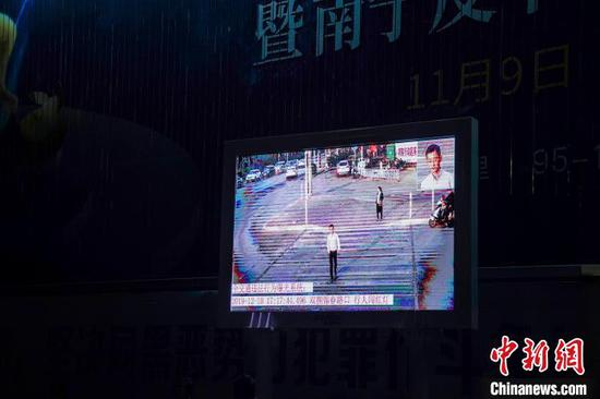 """12月10日,工作人员饰演被现场显示屏曝光警示的""""闯红灯行人""""。 陈冠言 摄"""