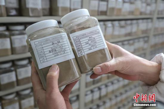 """12月10日,""""土壤檔案館"""" 工作人員在核對土壤樣品信息。當日,記者探訪了位貴州貴陽烏當區的貴州省耕地質量地球化學調查評價副樣庫。該庫是一個集土壤樣品存儲和數據管理系統于一體的智能化""""土壤檔案館"""",館內擺放著來自貴州88個縣(市、區)的47萬件土壤樣品, 該館可實現對土壤樣品采集點信息、存儲位置信息的規范化管理,同時能方便快捷地獲取土壤樣品及相關數據等信息。中新社記者 瞿宏倫 攝"""