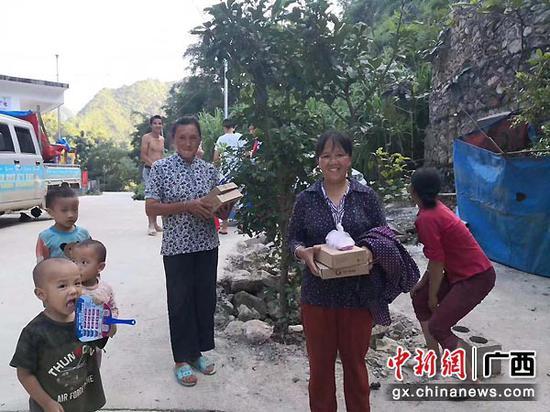图为乡村农户欢喜地领到广电云盒。