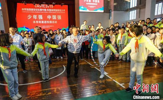 12月12日,奥运会体操冠军李小双(中)与同学们开展体育互动。 唐梦宪 摄