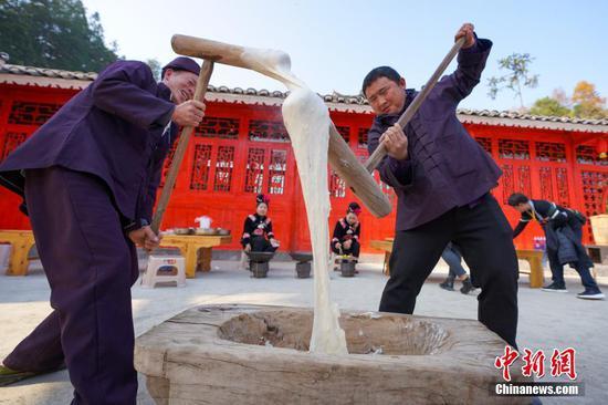 12月13日,两位侗族村民在打糍粑。当日是贵州省榕江县乐里七十二侗寨侗族民众欢庆侗族新年的日子。中新社记者 贺俊怡 摄