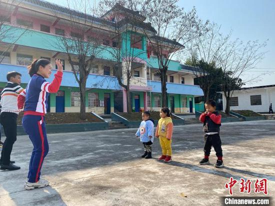 图为凯里市炉山镇甘坝村甘坝村幼儿园里,老师和3个孩子在室外活动。 刘鹏 摄