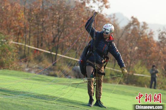 图为海外运动员在整理滑翔伞。 瞿宏伦 摄