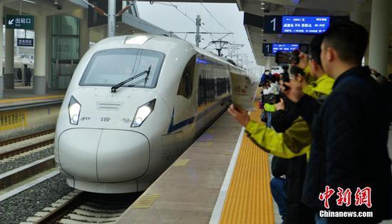 12月16日,随着开往成都南的C6008次动车驶出贵阳北高铁站,标志着成都至贵阳高铁(简称成贵高铁)宜宾至贵阳段开通运营,成贵高铁全线通车,成都与贵阳两个省会城市最快2小时58分可达。图为成都东首发的C6041次列车抵达宜宾西站,吸引民众拍照。中新社记者 刘忠俊 摄