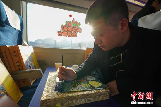 12月16日,随着开往成都南的C6008次动车驶出贵阳北高铁站,标志着成都至贵阳高铁(简称成贵高铁)宜宾至贵阳段开通运营,成贵高铁全线通车,成都与贵阳两个省会城市最快2小时58分可达。图为来自贵州大方县的农民画家进行绘画展示。中新社记者 贺俊怡 摄