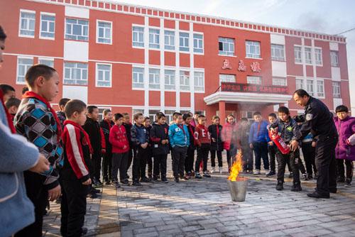民警手把手教育孩子们正确使用碳粉灭火器