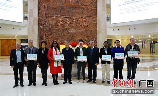圖為廣西國際壯醫醫院負責人與參加活動的嘉賓為在桂工作的6位外國專家代表頒發廣西外國專家友善醫院就診卡。孟娟娟 攝